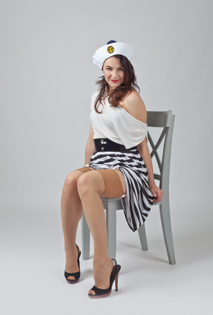 Photo pour Beautiful woman in pin up style with perfect hair and make up in sailor costume .Expressive facial expressions. - image libre de droit