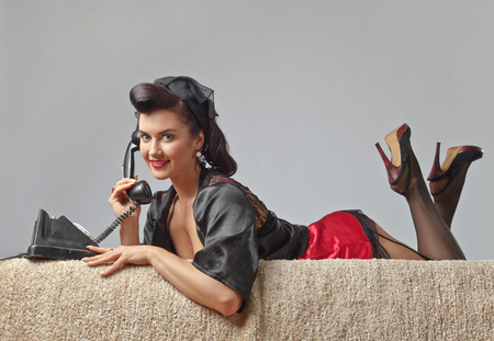 Photo pour Beautiful woman in pin up style with perfect hair and make up speaking via vintage phone.Expressive facial expressions. - image libre de droit
