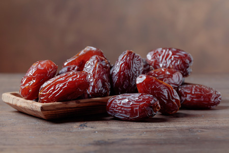 Foto de Juicy dates in a bowl on a old wooden table . - Imagen libre de derechos