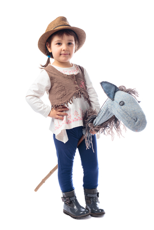 Photo pour Cute little girl dressed like a cowboy playing with a homemade horse. Isolated on a white background. Expressive facial expressions. - image libre de droit