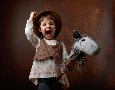 Photo for Cute little girl dressed like a cowboy playing with a homemade horse. Expressive facial expressions. - Royalty Free Image