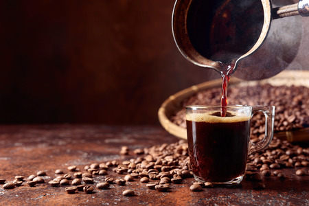 Photo pour Black coffee is poured into a small glass cup from a old copper coffee maker. Copy space. - image libre de droit