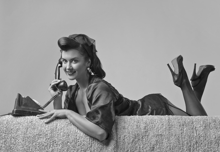 Foto de Beautiful brunette woman in pin up style speaking via vintage phone. Attractive young woman in 50s style with perfect make-up and hairstyle. Black and white. - Imagen libre de derechos