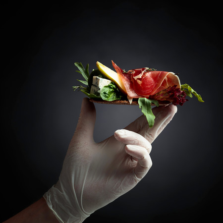 Photo for Conceptual image on the theme of fine food and delicacies. Rye cracker with blue cheese, prosciutto and pear garnished with greens. Compliment from the chef. - Royalty Free Image