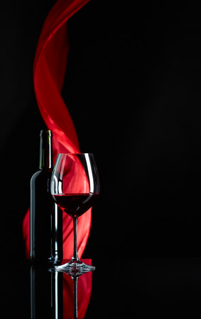 Photo pour Wineglass and bottle of red wine on a black reflective background. Red satin curtain flutters in the wind. Copy space. - image libre de droit