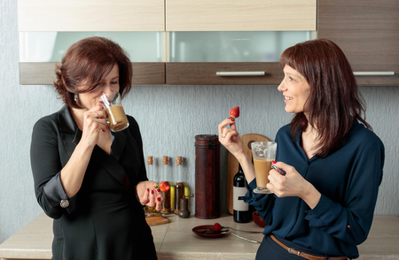 Photo for Two middle-aged girlfriends talk and drink coffee in the kitchen. - Royalty Free Image