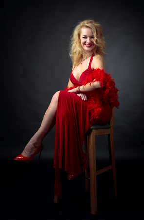 Foto de Attractive smiling mature woman  in red evening dress with fluffy feather boa. Happy forty years blonde on a black background. - Imagen libre de derechos