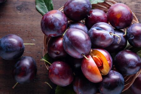 Foto de Ripe juicy plums on a old wooden table. Top view, copy space. - Imagen libre de derechos