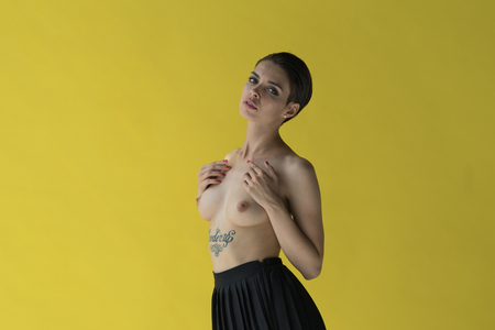 Photo for young beautiful girl posing nude in studio, standing in black skirt near yellow wall - Royalty Free Image