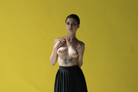 Photo for young beautiful girl posing nude in studio, standing near yellow wall in black skirt - Royalty Free Image
