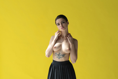 Foto de young girl posing in black underwear near the yellow wall - Imagen libre de derechos