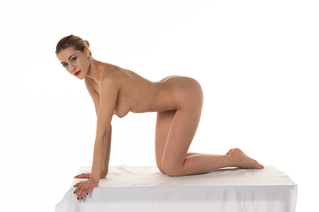 Photo for young beautiful girl posing nude in studio sitting on white table - Royalty Free Image