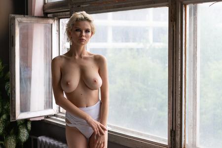 Foto de young beautiful girl posing in white underwear near the window - Imagen libre de derechos