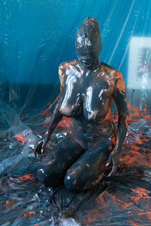 Photo pour young beautiful girl doused with black paint - image libre de droit