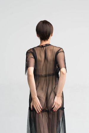 Foto de young beautiful girl stands in a black transparent dress in the studio - Imagen libre de derechos