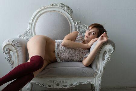 Foto de young beautiful girl pose nude in studio sitting on armchair - Imagen libre de derechos