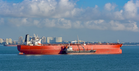 Photo pour Refuelling or bunkering in marine terms is carried out using a small tanker to pump the bunker fuel into the bigger ship. - image libre de droit