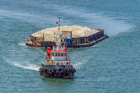 Foto de The tug boat towing a barge with sand in coastal waterway near Singapore - Imagen libre de derechos