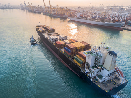 Photo for commercial vessel container ship in proceeding arrival to the port channel due, assist by the tugs boat for safety entrance gateway of the port - Royalty Free Image