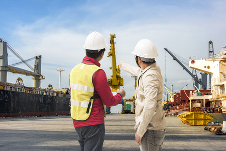Photo for Port and safety controler surveying the port terminal with ship berthing wharf in background - Royalty Free Image