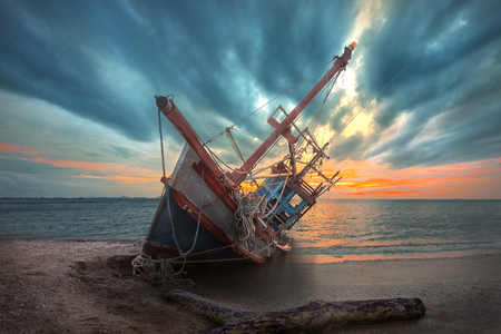 Foto de an old useless fishing boat laying dead on the sea beach at sunset scenery in background - Imagen libre de derechos