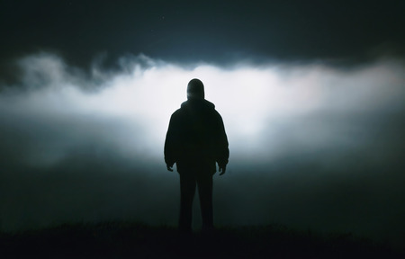 Foto per Silhouette of a man in the darkness. Night Photography. Dense fog over the river. - Immagine Royalty Free