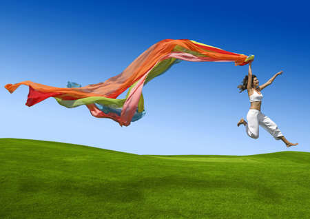Foto de Athletic woman jumping on a green meadow  - Imagen libre de derechos