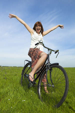 Happy young woman relaxing over a vintage bicycle