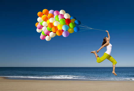 Photo pour Beautiful and athletic girl with colorful balloons jumping on the beach  - image libre de droit