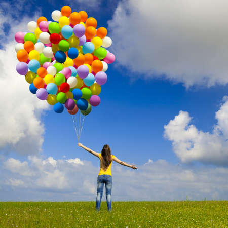 Foto de Happy young woman with colorful balloons on a green meadow - Imagen libre de derechos