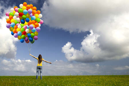 Photo for Happy young woman with colorful balloons on a green meadow - Royalty Free Image