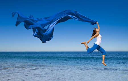 Foto de Beautiful young woman jumping on the beach with a colored tissue  - Imagen libre de derechos
