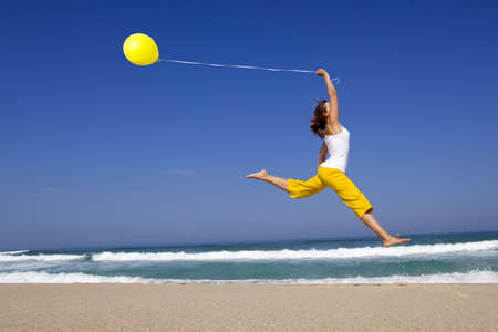 Photo pour Beautiful and athletic Girl jumping with a balloon on the beach - image libre de droit