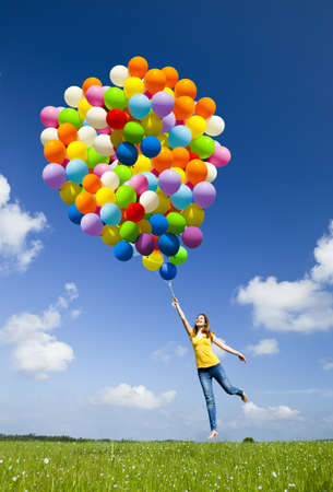 Photo pour Happy young woman holding colorful balloons and flying over a green meadow - image libre de droit