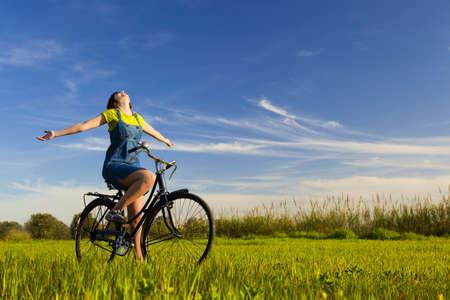 Foto de Happy girl over a bicycle and looking the view, in a green meadow - Imagen libre de derechos