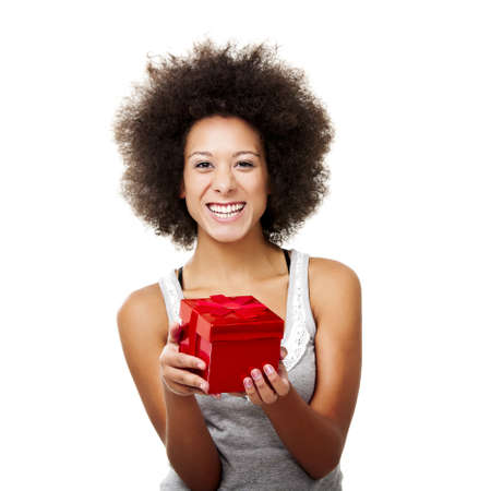 Beautiful happy young woman holding a red christmas gift, isolated on white