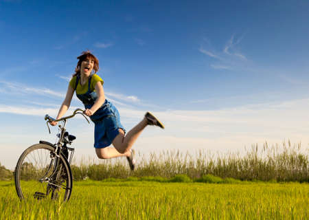 Photo pour Happy woman  with a old bicycle in a green meadow and jumping - image libre de droit