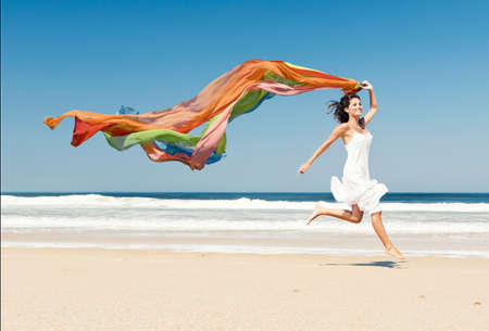 Photo pour Beautiful girl in the beach running and holding a colored piece of fabric - image libre de droit