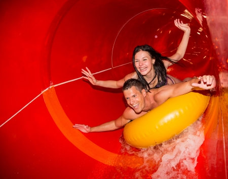 Photo for Couple cheering while having fun sliding down a water slide at public swimming pool - Royalty Free Image