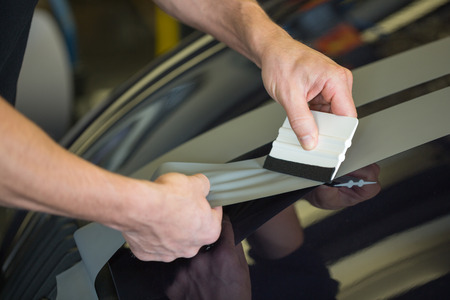 Photo pour Car wrapper straightening wrapping foil with a squeegee to remove air bubbles - image libre de droit