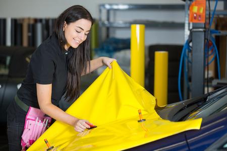 Foto de Car wrapping specialists straightening vinyl foil or film to remove ari bubbles - Imagen libre de derechos