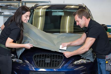 Photo pour Car wrappers using squeegee to straighten vinyl foil  - image libre de droit