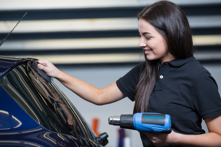 Foto de Car wrapper using heat gun and squegee for tinting a window - Imagen libre de derechos