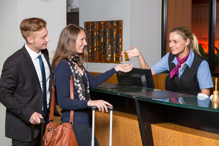 Photo pour receptionist at hotel reception handing over a key to guest or customer - image libre de droit