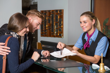 Photo for receptionist at hotel showing guest something on a map - Royalty Free Image