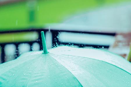 Raindrops falling over an umbrella.