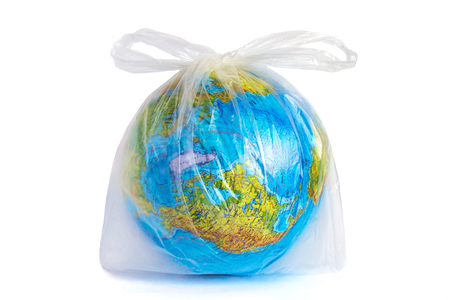Foto de Model planet Earth (globe) in polyethylene plastic disposable package, isolated on white background. Ð¡oncept pollution of environment with polyethylene plastic waste, ecological problem - Imagen libre de derechos