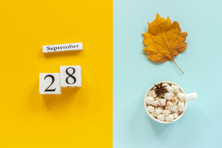Photo pour Autumn composition. Wooden calendar September 28, cup of cocoa with marshmallows and yellow autumn leaves on yellow blue background. Top view Flat lay Mockup Concept Hello September. - image libre de droit