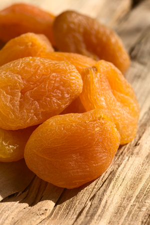 Photo for Dried apricots, a healthy snack containing vitamin, beta-carotene, fiber, antioxidants, photographed on wood with natural light (Selective Focus, Focus on the first apricot) - Royalty Free Image