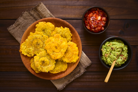 Photo pour Patacon or toston, fried and flattened pieces of green plantains, a traditional snack or accompaniment in the Caribbean, guacamole and tomato and onion salad on the side, photographed overhead on dark wood with natural light - image libre de droit